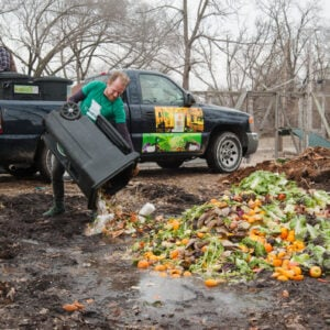 John Taube, a member of the Green Team dumps scraps to compost compost at the farm on Saturday, March 2, 2019.  (Photo by Stephen Bybee)